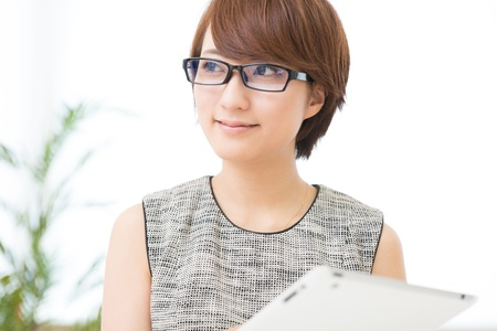 Beautiful young asian woman using tablet computer photo