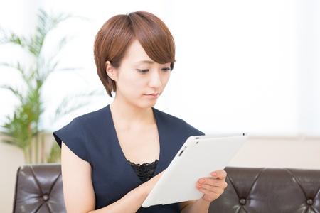 Beautiful young asian woman using tablet computer 版權商用圖片
