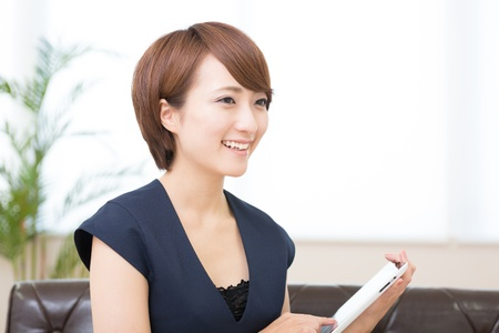Beautiful young asian woman using tablet computer Imagens