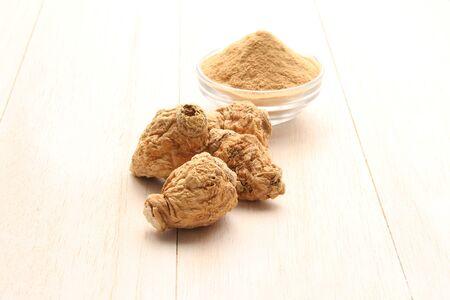 Maca root and maca powder on white wood background.