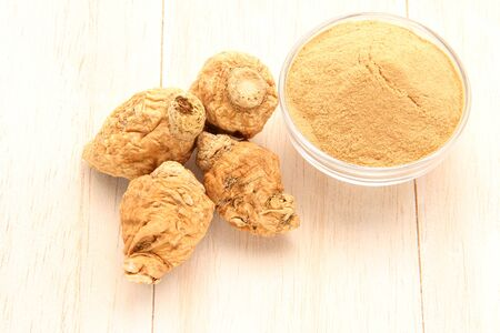 Maca root and maca powder, on white wood background. (Taken above)
