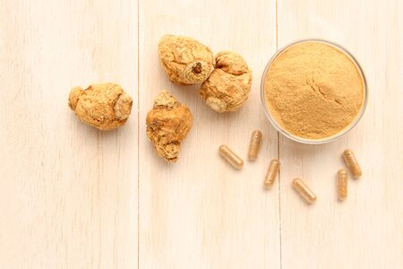 Maca root and maca powder and capsules, on white wooden background. (Taken above) Stock Photo