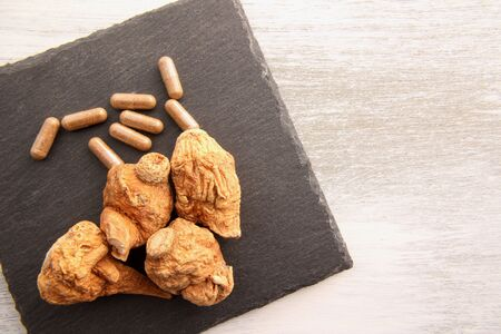 Dried maca and maca capsules on a stone plate. Stock Photo