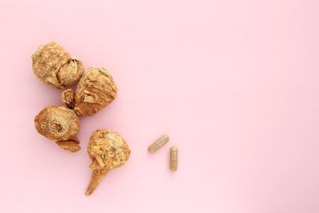 Maca root and maca powder capsule on light pink background.