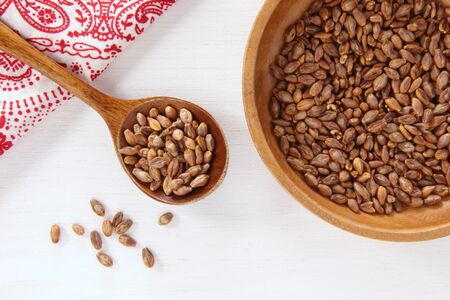 Super barley on a wooden dish and wooden spoon.