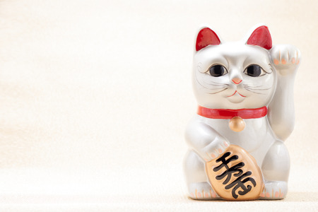 maneki: Japanese silver beckoning cat called Manekineko also known as a lucky cat
