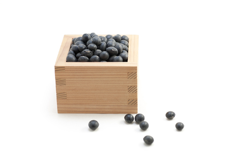 protein crops: Black beans in Japanese sake cup called Masu on white isolated background