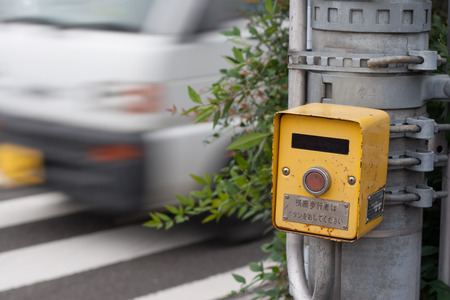 cross street with care: Japanese pedestrian control signal at zebra zone as a car passing by
