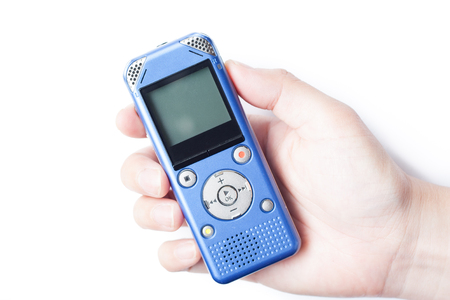 Holiding IC recorder by hand on white isolate background