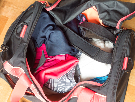 wrist strap: Top view of the inside of the girls gym bag containing sports equipments such as clothes, towel and wrist strap Stock Photo