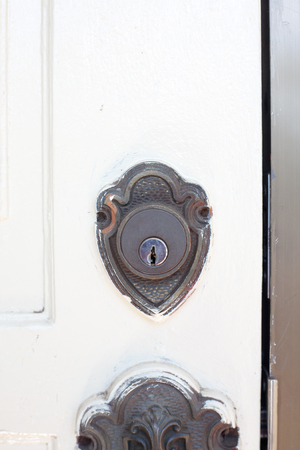antique keyhole: Antique brass keyhole of a white painted entrance door