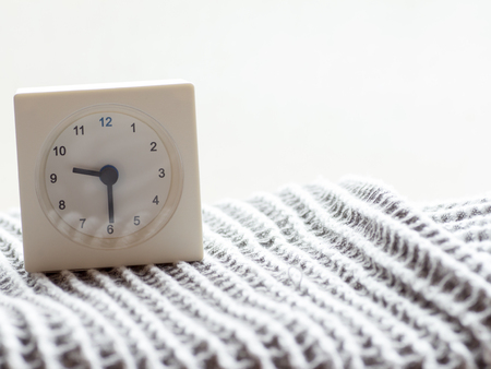 continuation: The series of a simple white analog clock on the blanket that depicts time in the morning 1015 Stock Photo
