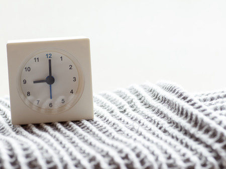 continuation: The series of a simple white analog clock on the blanket that depicts time in the morning 915 Stock Photo