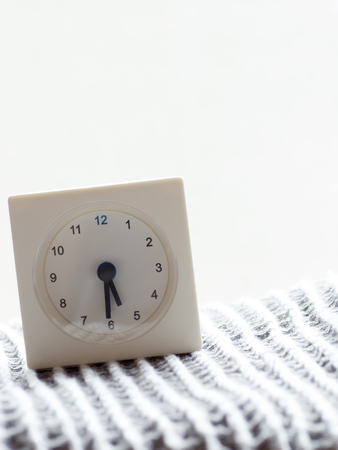 continuation: The series of a simple white analog clock on the blanket that depicts time in the morning 215 Stock Photo