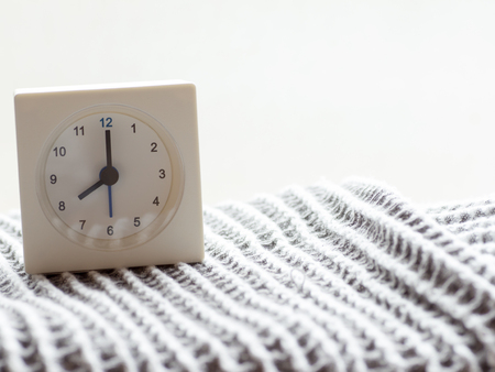 just in time: The series of a simple white analog clock on the blanket that depicts time in the morning 715 Stock Photo