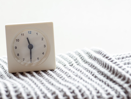 continuation: The series of a simple white analog clock on the blanket that depicts time in the morning 1415