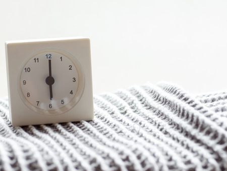 continuation: The series of a simple white analog clock on the blanket that depicts time in the morning 315 Stock Photo