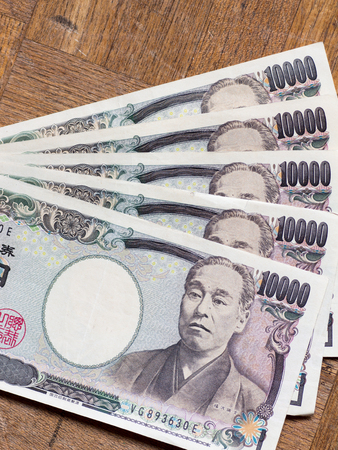spreaded: Spreaded some Japanese 10000 yen bills on the wooden board Stock Photo