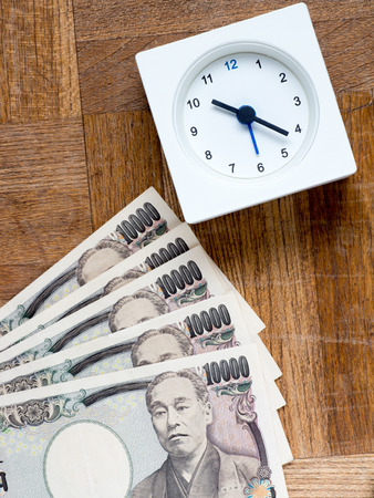spreaded: A clock and Japanese 10000 yen bills on the wooden table that depicts Time is money