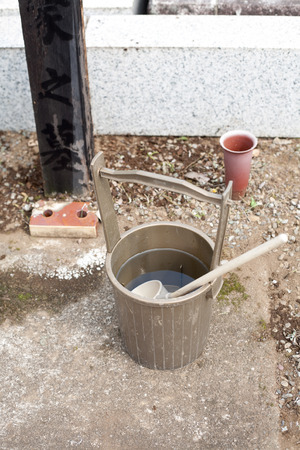 baptizing: Japanese religious bucket and ladle for purifying at the old grave yard Stock Photo