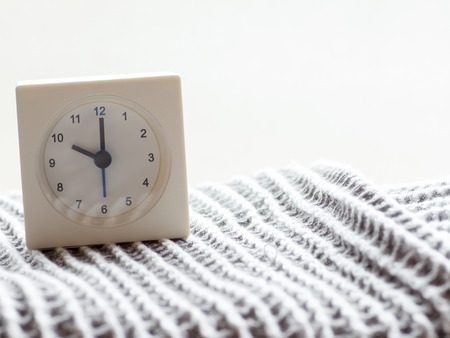continuation: The series of a simple white analog clock on the blanket that depicts time in the morning 1115 Stock Photo