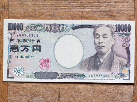 Top view of Japanese 10000 yen bill on the wooden board