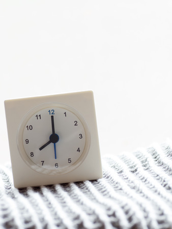 continuation: The series of a simple white analog clock on the blanket that depicts time in the morning 715 Stock Photo