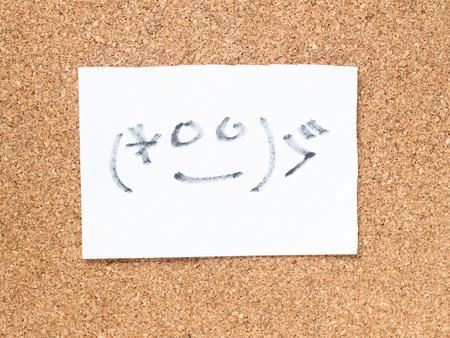 コルク板に顔文字と呼ばれる日本のエモティコンのシリーズが恥ずかしい
