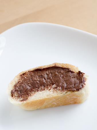 Piece of french bread with chocolate peanut butter on a white dish plate