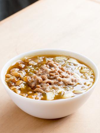 木製のテーブルに納豆とカレーそば、日本料理