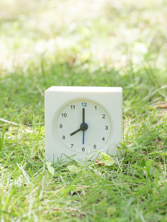 White rectangle simple clock on lawn yard, 8:00 eight oclock Stock Photo