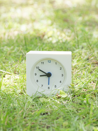 White rectangle simple clock on lawn yard, 8:50 eight fifty