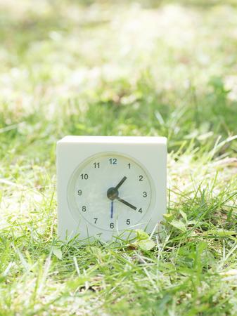 White rectangle simple clock on lawn yard,1:20 one twenty