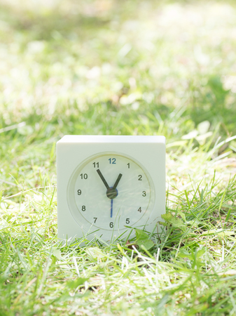 White rectangle simple clock on lawn yard, 12:55 twelve fifty five Stock Photo