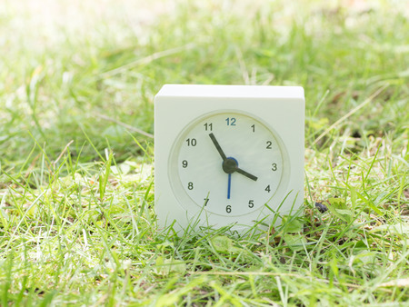 White rectangle simple clock on lawn yard, 3:55 three fifty five Stock Photo