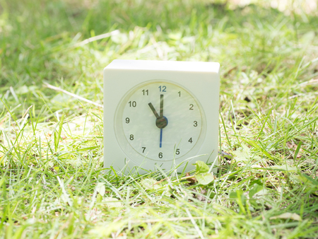 White rectangle simple clock on lawn yard, 11:00 eleven oclock