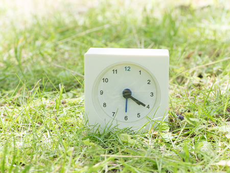 White rectangle simple clock on lawn yard, 4:20 four twenty Stock Photo