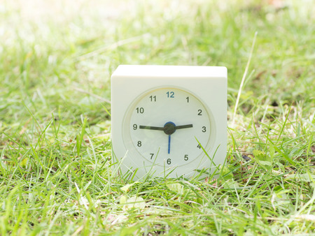 White rectangle simple clock on lawn yard, 2:45 two forty five