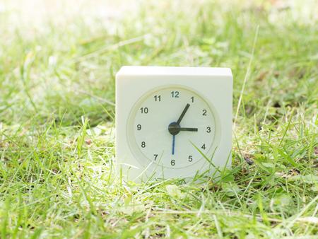 White rectangle simple clock on lawn yard,  3:05 three five Stock Photo