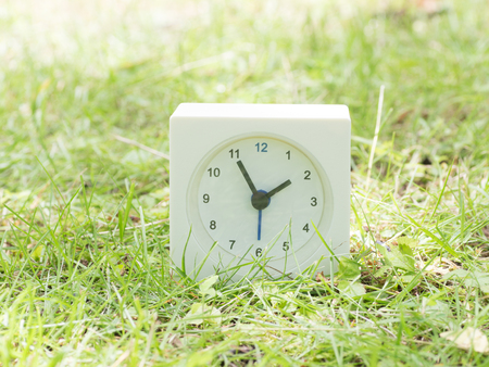 White rectangle simple clock on lawn yard,1:55 one fifty five Stock Photo