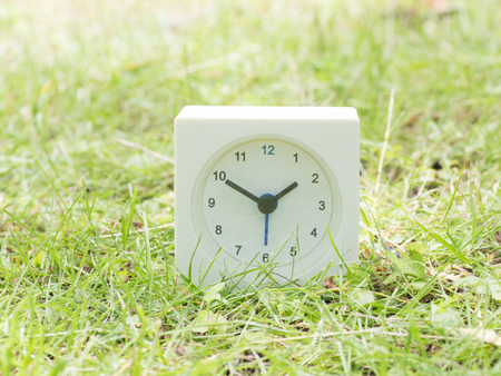 White rectangle simple clock on lawn yard, 1:50 one fifty