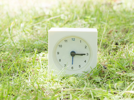 White rectangle simple clock on lawn yard,  3:15 three fifteen Imagens