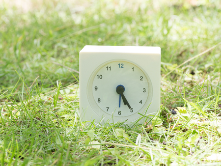 White rectangle simple clock on lawn yard, 5:25 five twenty five
