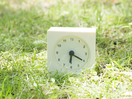 White rectangle simple clock on lawn yard, 6:20 six twenty Stock Photo