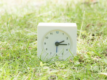 White rectangle simple clock on lawn yard, 2:15 two fifteen Stock Photo