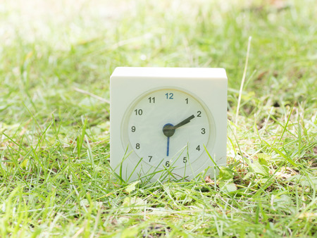 White rectangle simple clock on lawn yard,2:10 two ten Stock Photo