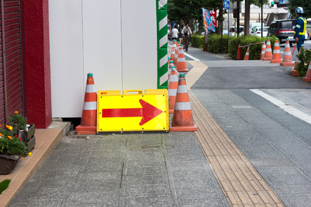 Red and yellow arrow sign indicating a detour on the Japanese construction site