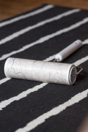 Dirty lint roller on a black and white carpet Stock Photo