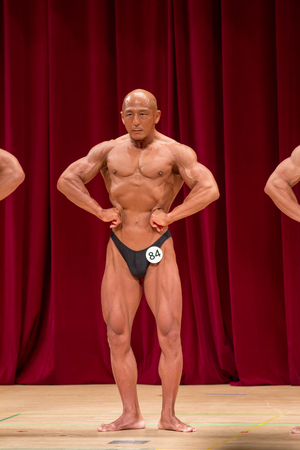 Japanese bulky bald head male 50s bodybuider posing front lat spread Stock Photo