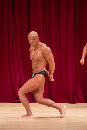 Japanese bulky bald head male 50s bodybuider posing side triceps Stock Photo